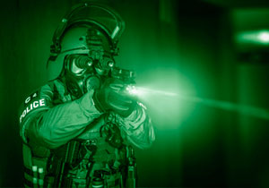An operator of a special police unit with night vision googles firing with a pistol.