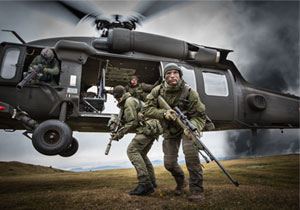 Two special operations forces scout snipers are dropped by a blackhawk helicopter.
