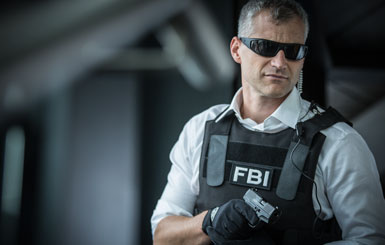 An FBI officer with a pistol at the ready.