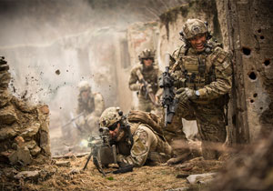 Special operations forces soldiers in a combat mission between house ruins.