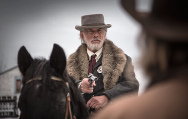 A marshal on his horse with his revolver at the ready.