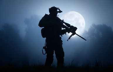 A sniper with night vision goggles and sniper rifle in the moonlight.